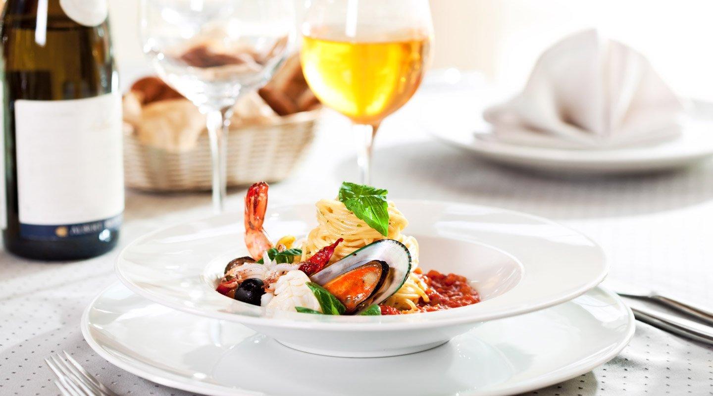 spaghetti di pesce con calice di vino bianco