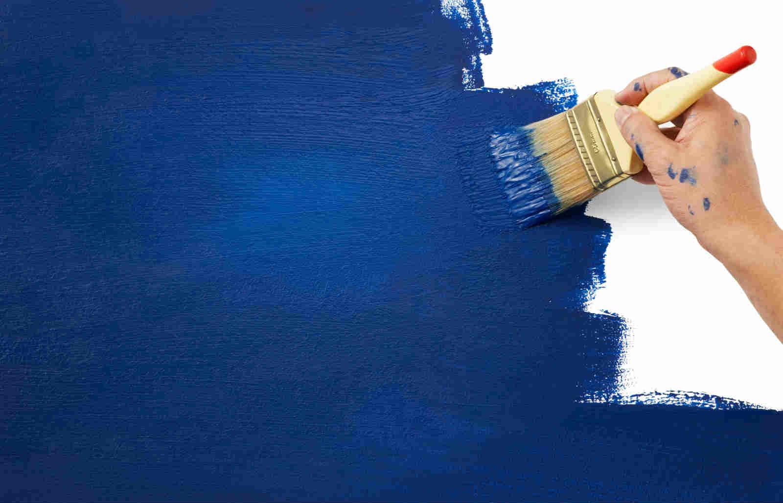 Mano con pennello grande imbiancando la parete di blu