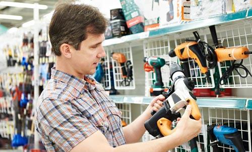 uomo mentre acquista per perforatore in negozio di ferramenta