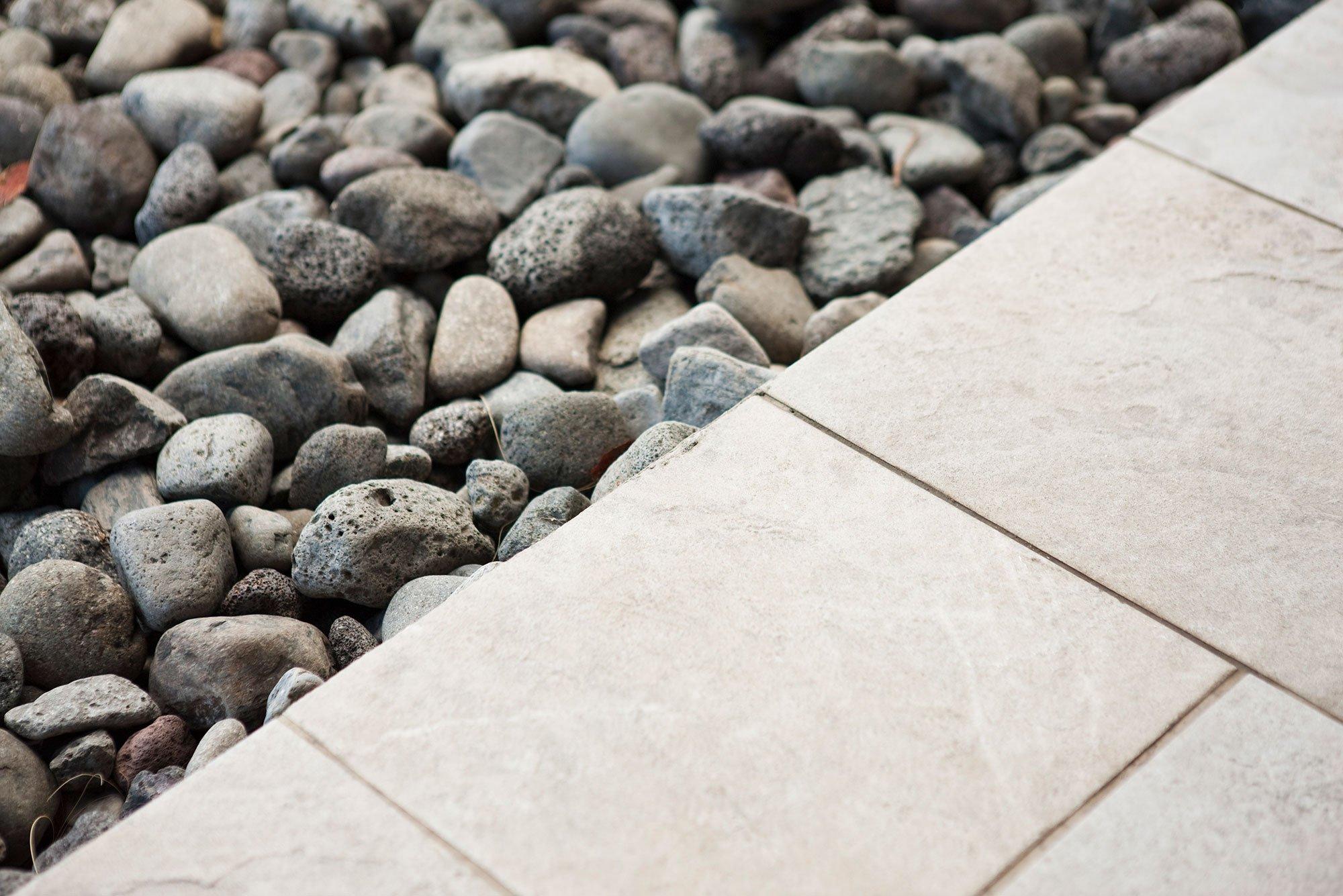 Gravel along edge of tiled patio