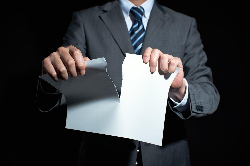 uomo che straccia un foglio di carta