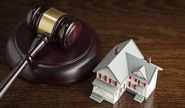 Gavel and small model house to represent real estate law in Torrington