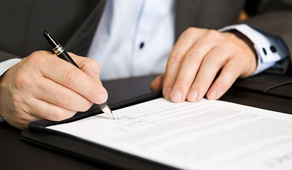 Un uomo con completo seduto alla scrivania, mentre firma un documento con una penna di color nero