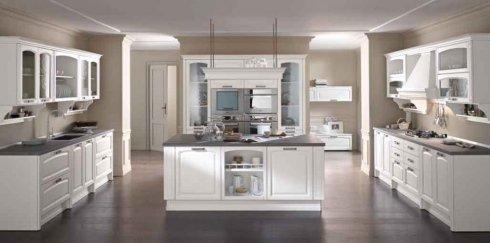 un'ampia cucina con mobili bianchi e penisola centrale