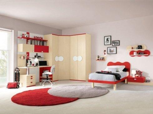 una cameretta con un letto rosso e un armadio angolare beige chiaro