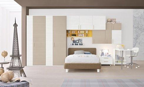 una cameretta con un letto e degli armadi beige e bianchi
