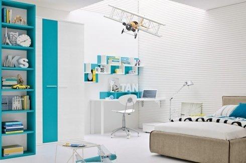 una cameretta con una scrivania, una sedia bianca ,un letto e una libreria azzurra