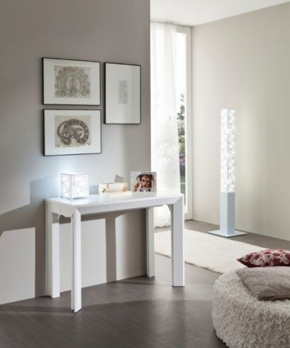 un tavolino bianco con sopra delle cornici e dei quadri al muro