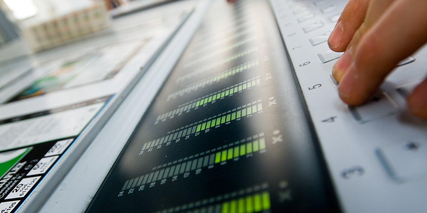 una mano che digita su una tastiera e uno schermo in cui sono visualizzati delle barre che indicano dei livelli