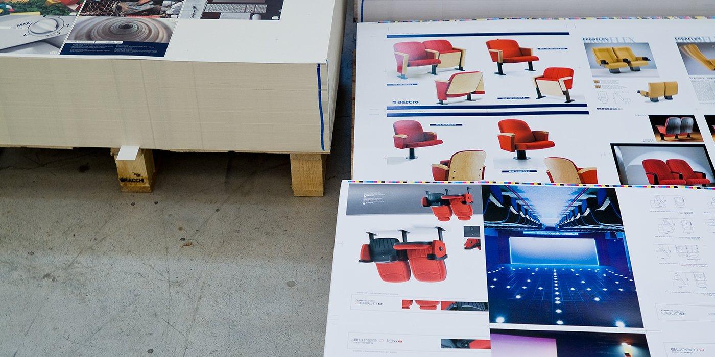 sulla sinistra una pila di fogli stampati su un bancale e sulla destra dei fogli stampati raffiguranti delle sedie rosse da ufficio e altre immagini