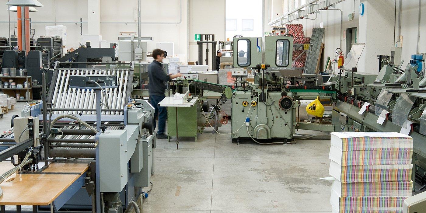 un uomo al lavoro all'interno di una fabbrica con macchinari per stampe grafiche