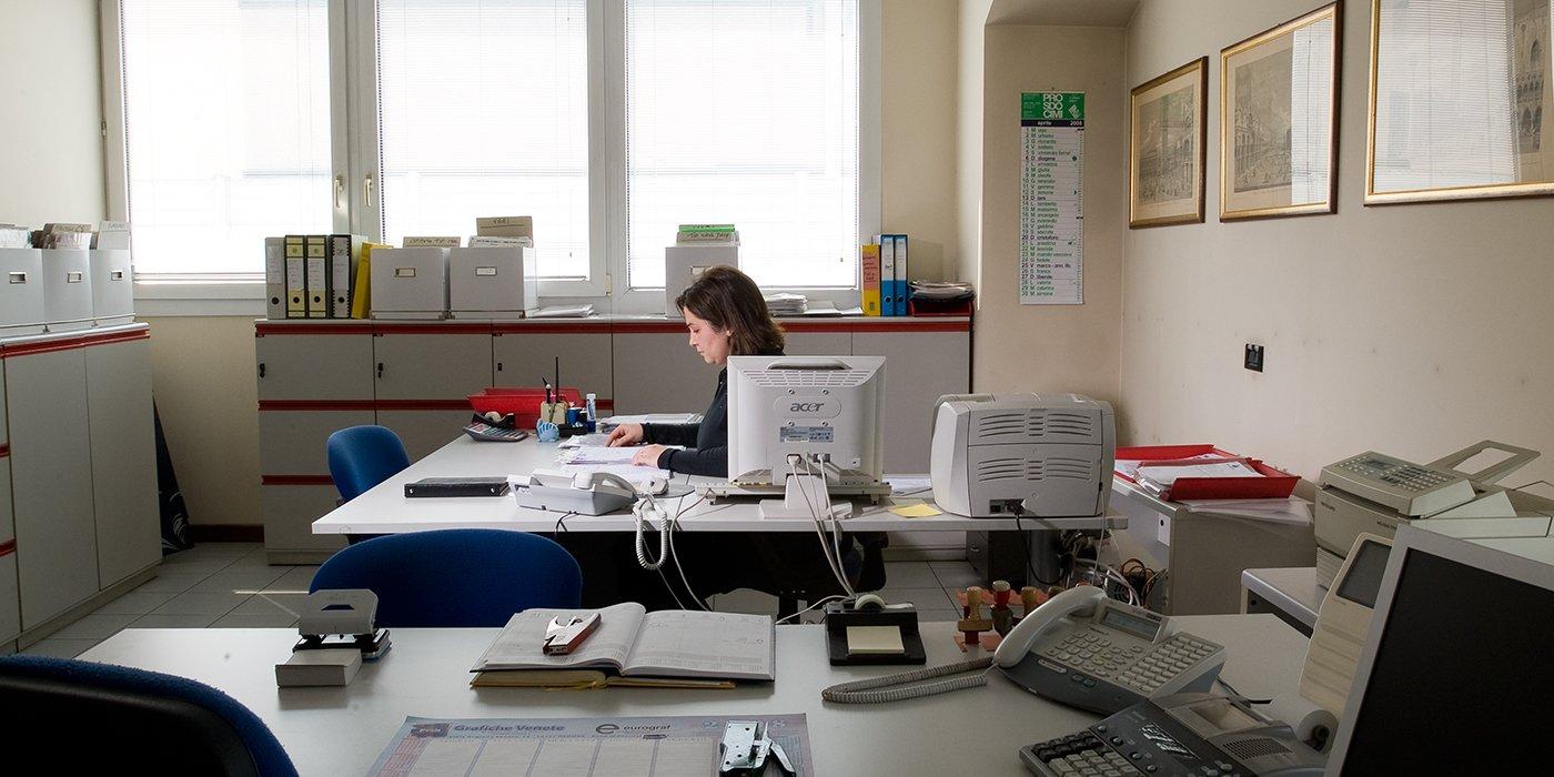 una donna alla scrivania mentre sistema dei documenti in un ufficio