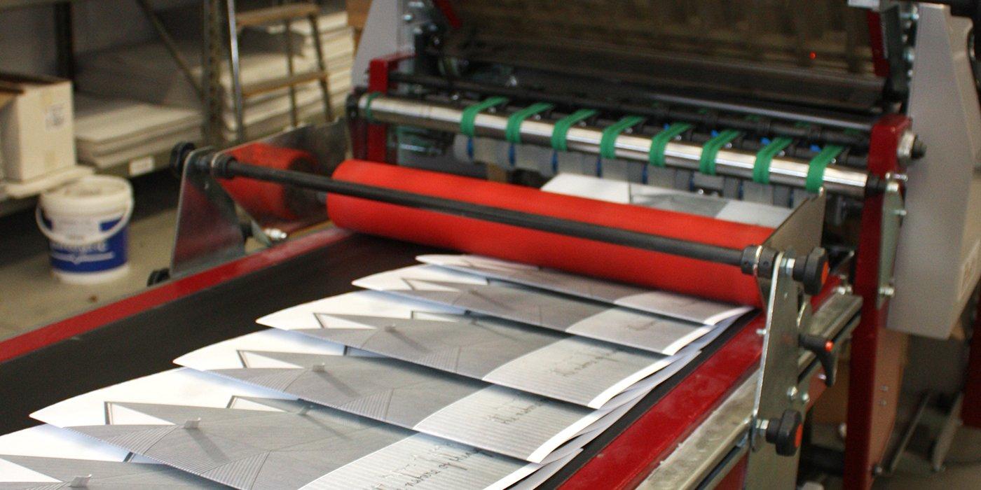 un macchinario da stampa e sotto dei fogli stampati Grafiche-venete-padova-015 - un macchinario da stampa