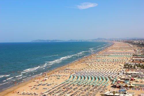 vista dall'alto del mare e di una lunga spiaggia con ombrelloni in Romagna