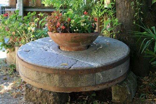 un vaso di fiori rossi sopra a una ruota in pietra
