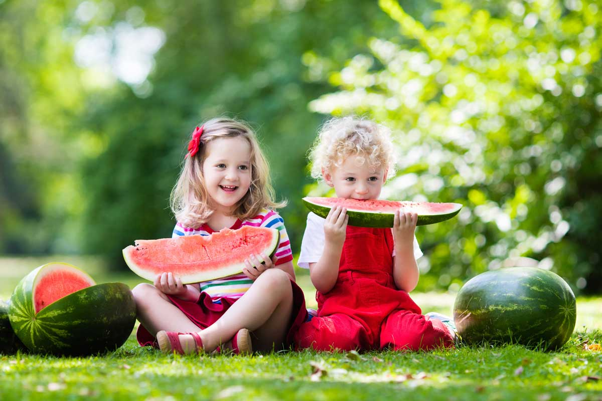 girls eating watermelon on the lawn