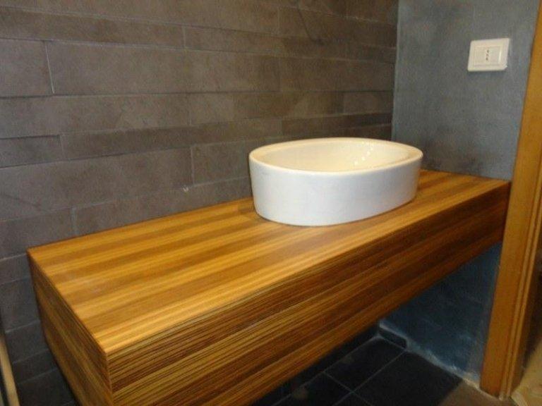 una mensola in legno con sopra un lavandino