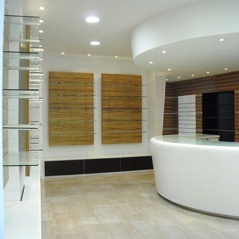 una reception a curva di color bianco con superficie in vetro