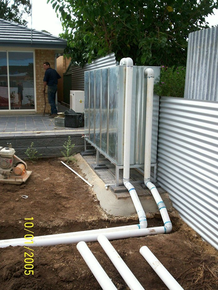 metal tank with multiple pipes routed through the yard