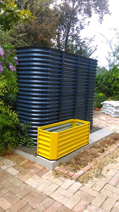 small yellow and large blue tank on cement slab
