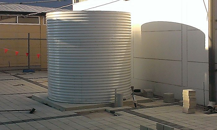 newly installed cream tanks with piping on platform