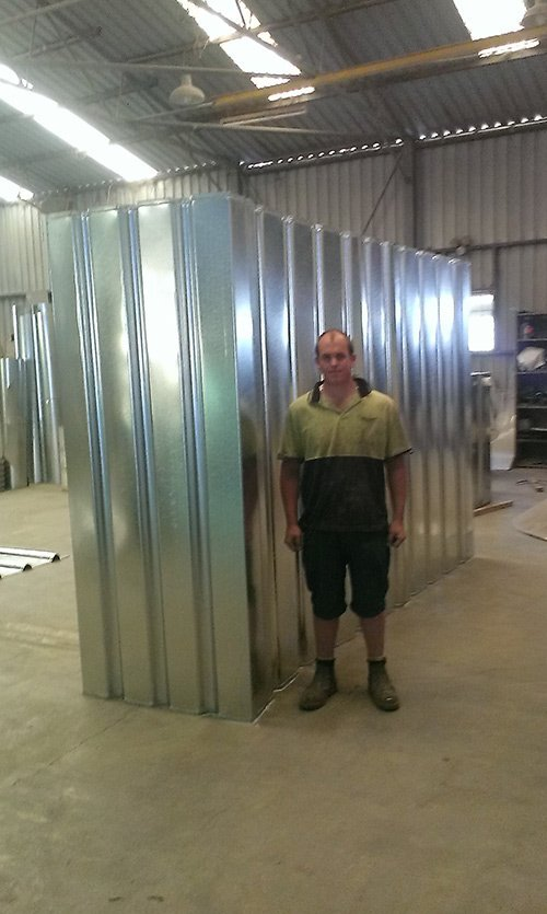 tall man standing next to metal container