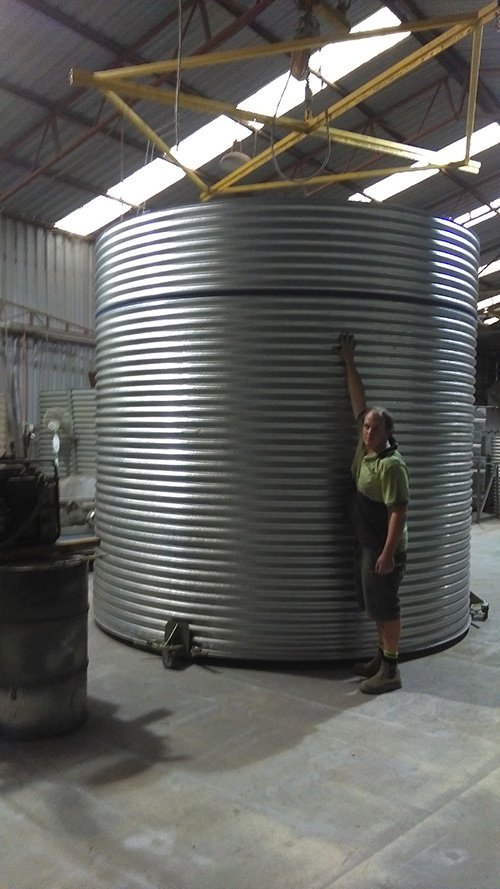 tall man standing next to water tank with arm high