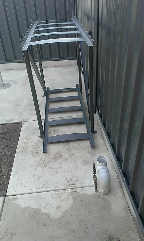 custom metal ladder sits next to piping for tank