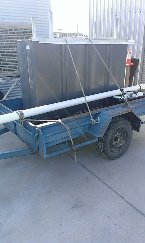 grey tank and pipe loaded on blue trailer