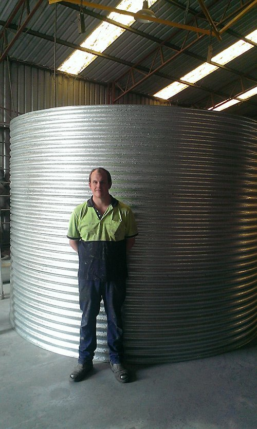 man with a silver cylinder water tank