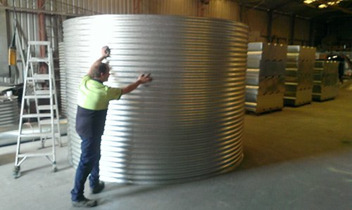 man touching a silver water tank