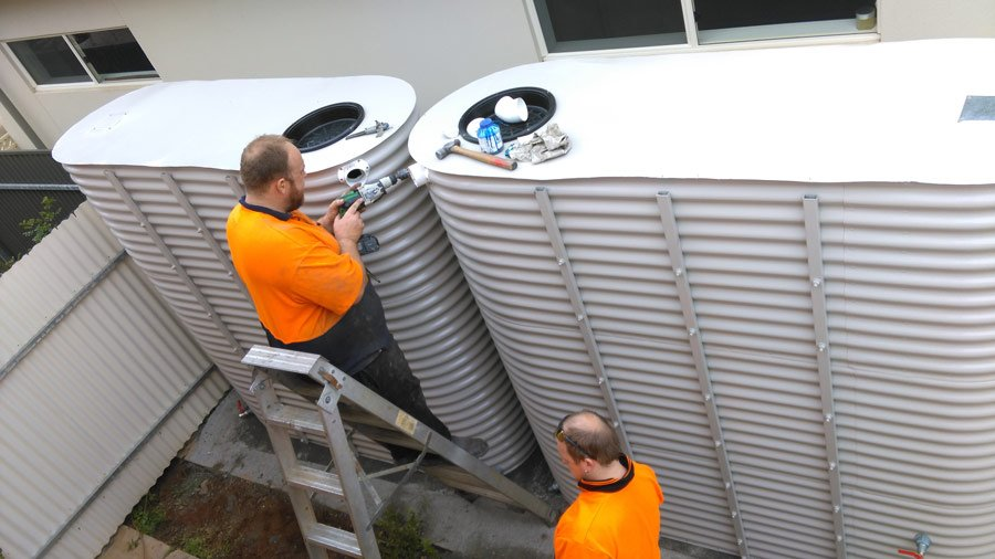 workers installing corrugated ultra slim tank