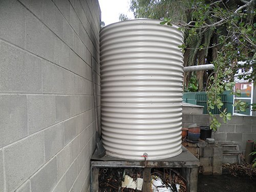 small white water tank with a grey brick wall