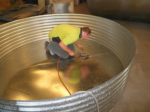 man working with a large metal circle