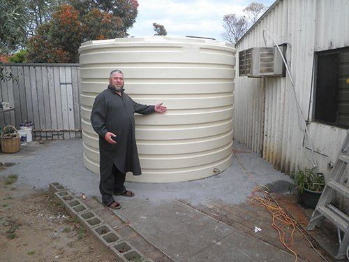 man standing next to a white water tank