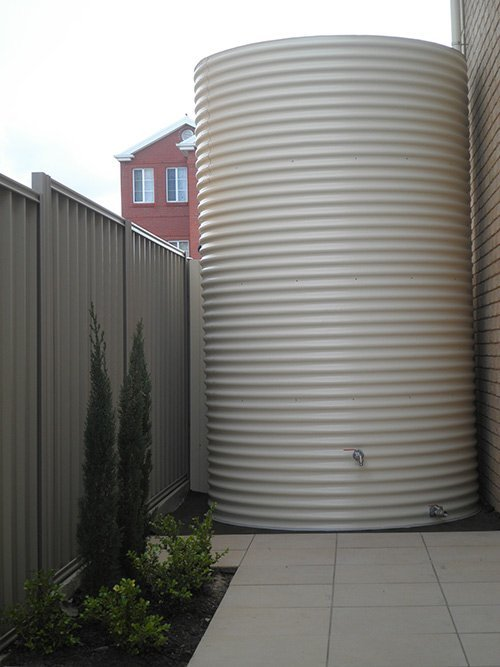 large white water tank and a grey brick wall