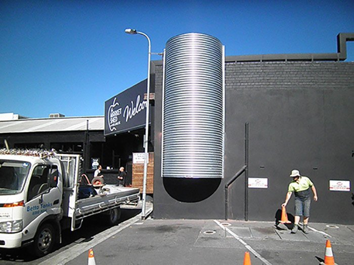 black building with a silver cylinder and a white truck