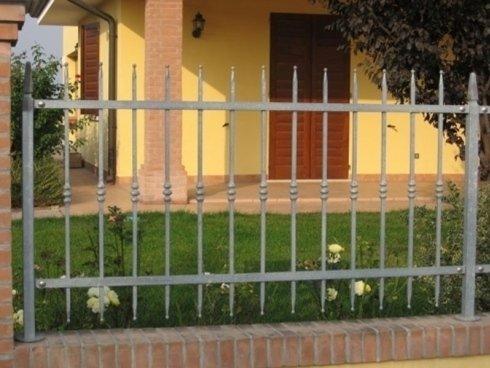 una recinzione in ferro e vista del giardino di una villa