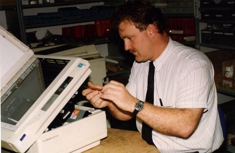 man working on photocopier