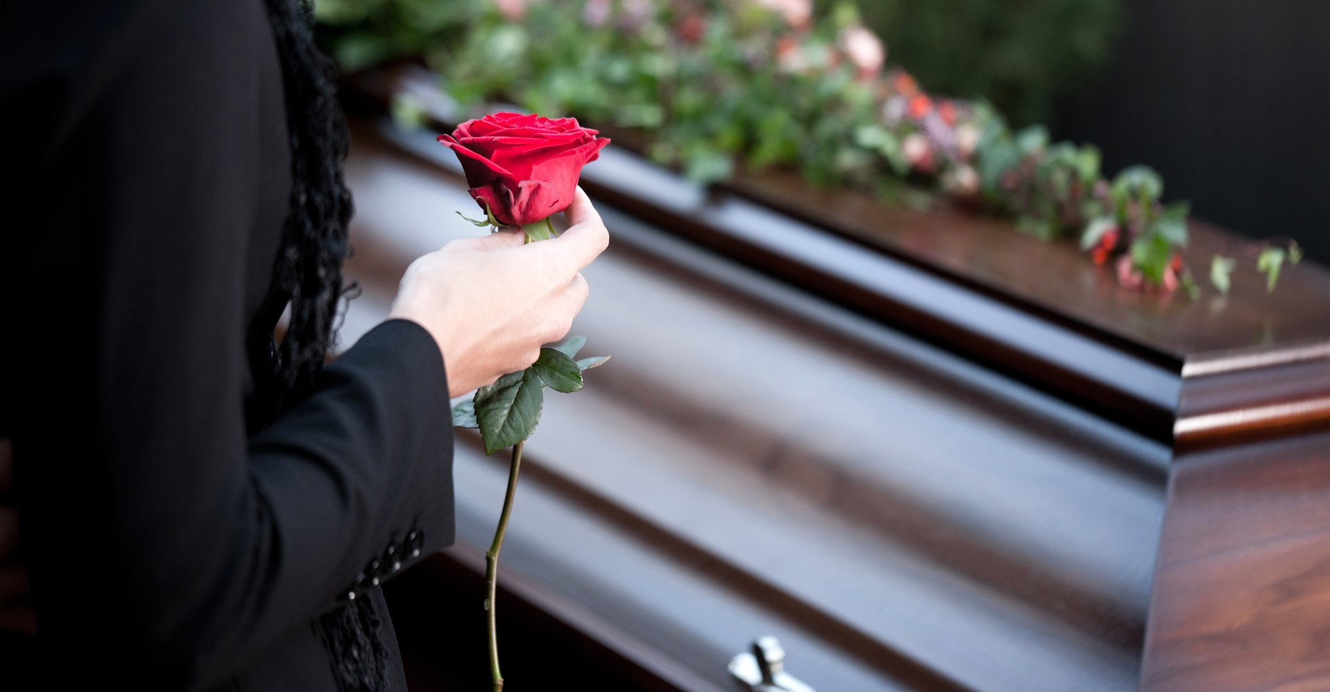 Woman holding a rose to place on a coffin box