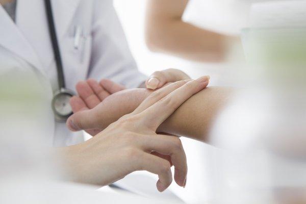 dottore controllando il battito sul polso ad una paziente
