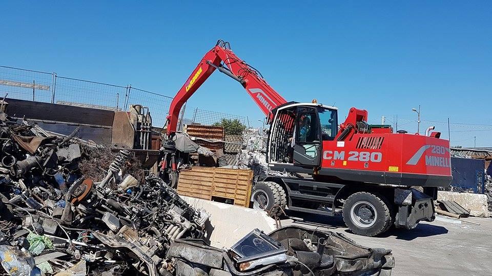 una demolitrice e delle pile di rottami