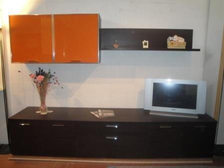 un mobile in legno con sopra una Tv e due ante di color arancione