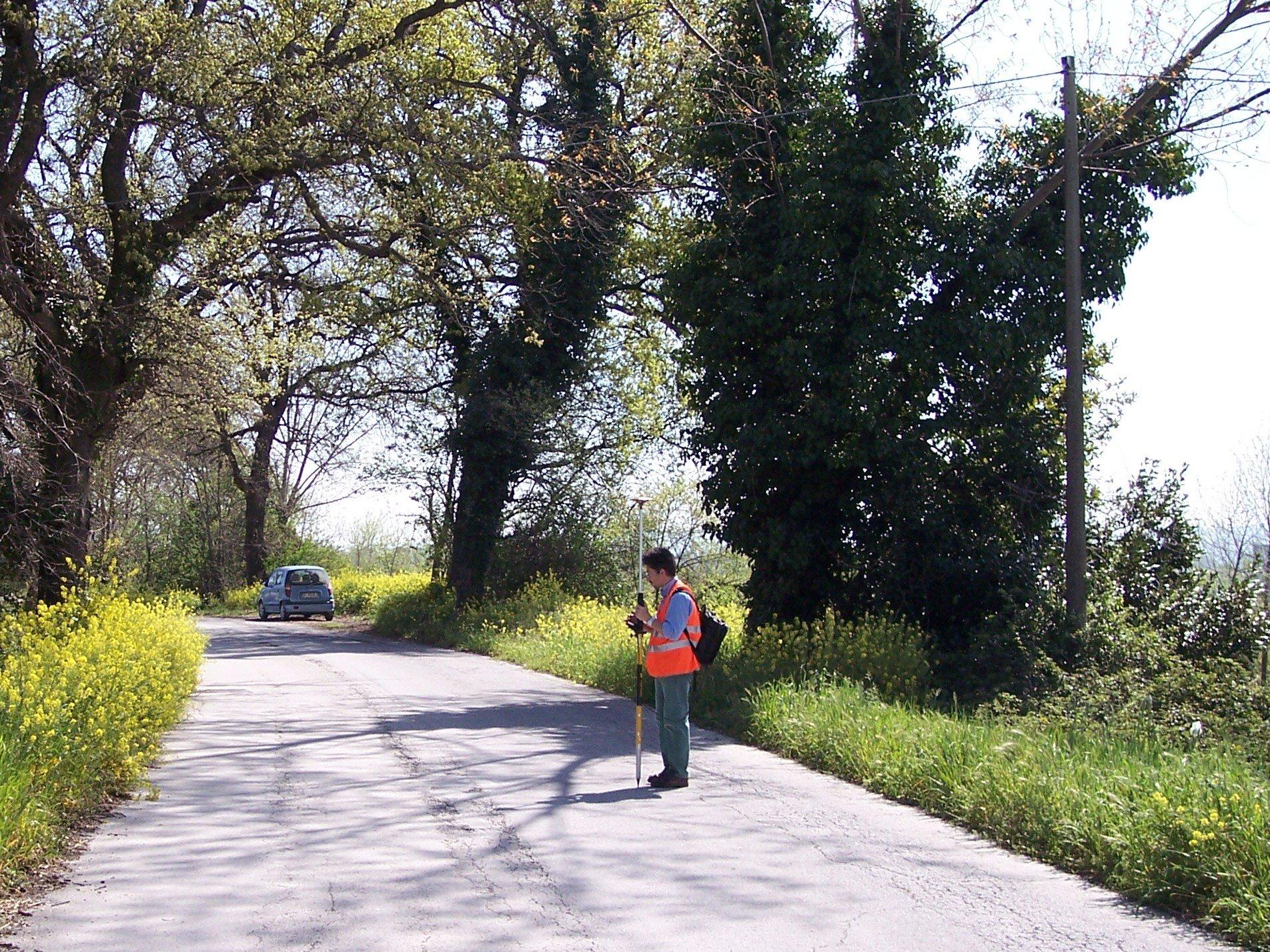 Un uomo utilizza uno strumento per rilievo topografico in strada