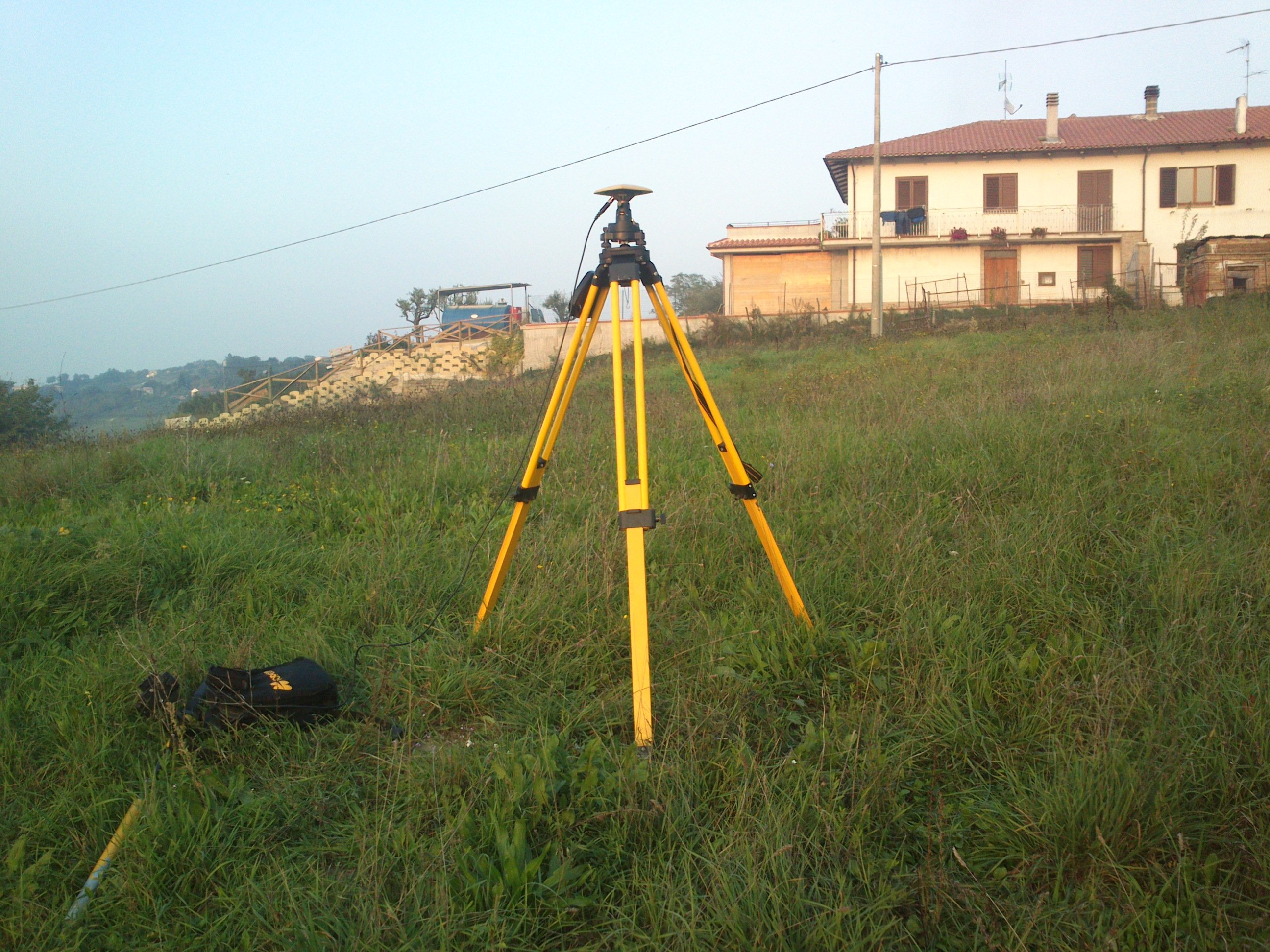 strumento geodetico in un prato con casa sullo sfondo