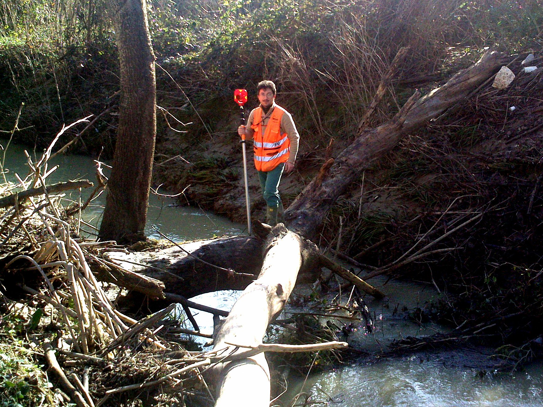 un uomo attraversa un ruscello camminando sul tronco di un albero caduto