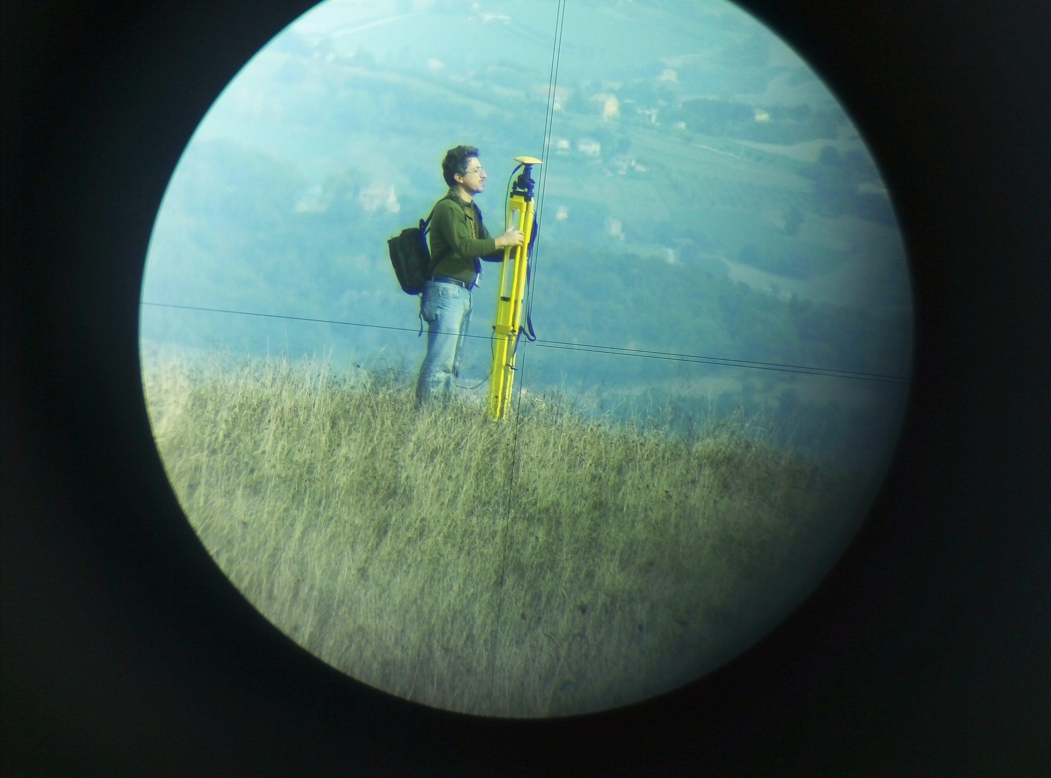 uomo ripreso da lontano mentre utilizza uno strumento per rilievo topografico