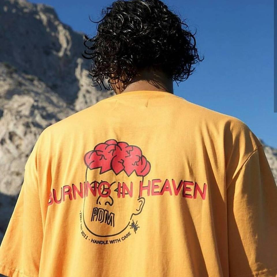 una maglietta gialla con la faccia di un ragazzo con capelli rossi ricci e la scritta burning in heaven