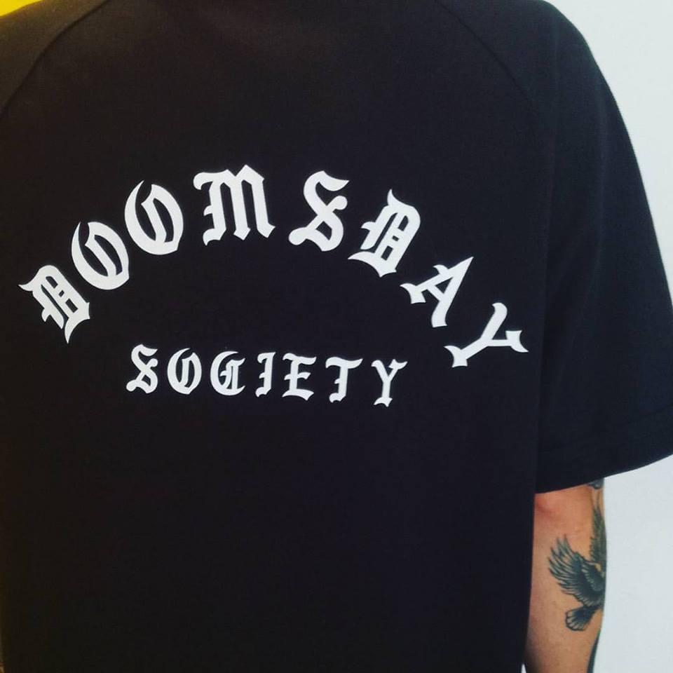 una maglietta nera con scritto Doomsday Society