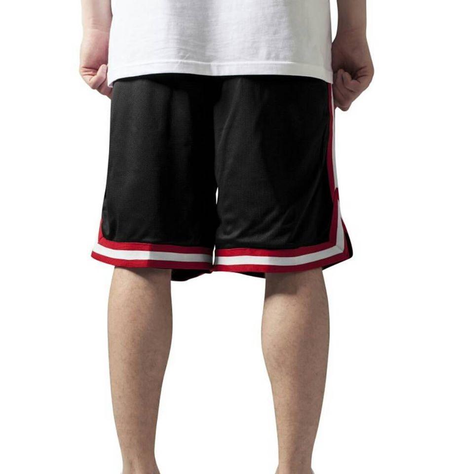 un ragazzo con una t shirt bianca e dei pantaloncini neri a righe bianche e rosse